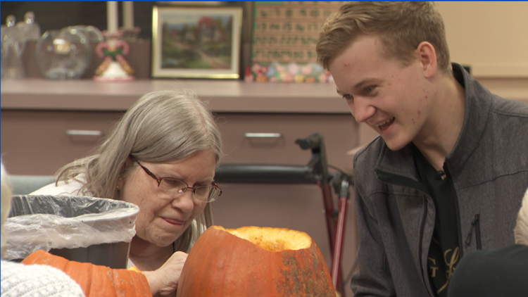Nancy Neumann carves a Halloween pumpkin with her neighbor, Winona State University student Joel Olson.  Both are residents of Senior Living at Watkins, an assisted living home in Winona.