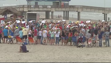 Human peace sign formed on Port Aransas beach to celebrate Earth Day