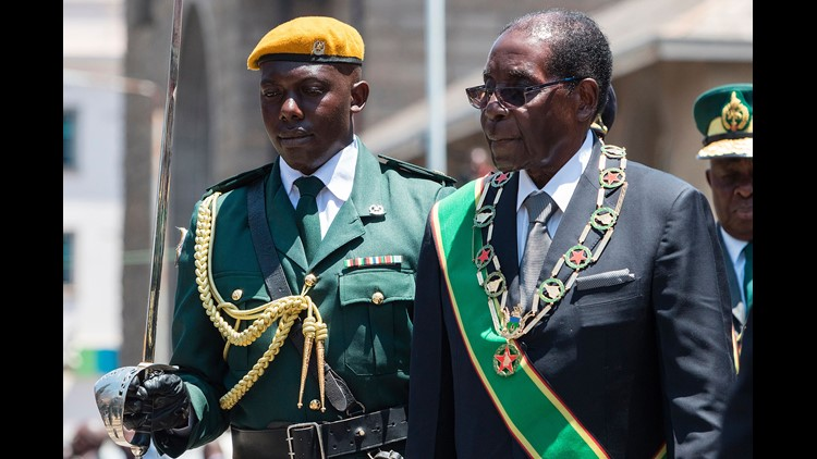 Zimbabwe's President Robert Mugabe (R) inspects an honor guard during the official opening of the fourth session of the eight Parliament of Zimbabwe on October 6, 2016 in Harare.